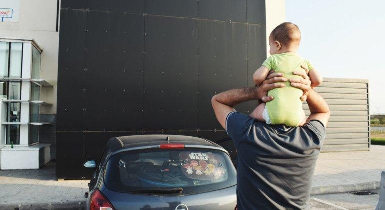 Papa con bebé a hombros en un viaje con niños pequeños