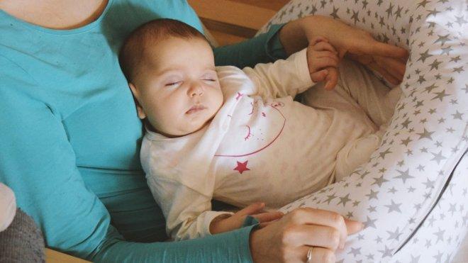 Mi bebé duerma mal o duerme bien, bebé en brazos de su madre durmiendo con cojin de lactancia