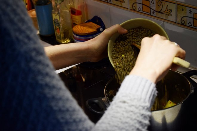 Vertiendo lentejas en olla para receta tradicional de lentejas con Caldo aneto de puchero