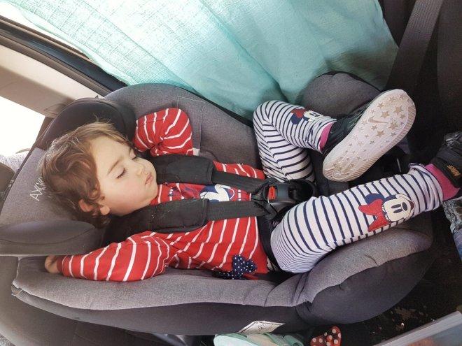 Bebé de 2 años durmiendo en su silla a contramarcha del coche, de camino al Mbday