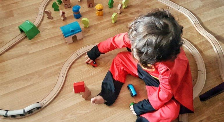 Niña de dos años jugando con un tren de madera, disfrazada de superheroe