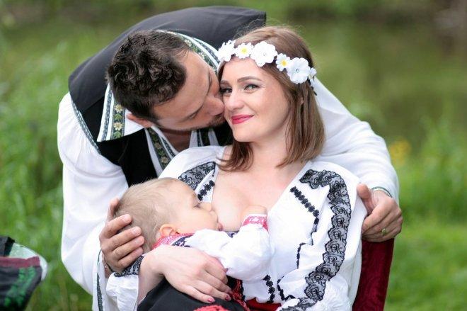 Padre besando a su pareja mientras ella amamanta a us bebé, el papel del padre en la lactancia materna como agente facilitador.