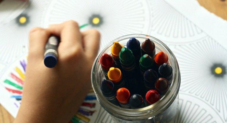 Mano de niño pintando con ceras en primer plano para el post han cambiado a mi hija de clase en la escuela infantil