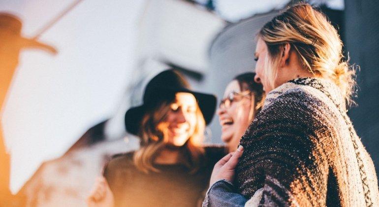 Grupo de mujeres hablando contentas, la importancia de la tribu en la crianza