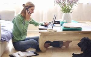 Une femme assise sur le sol entrain de consulter un ordinateur et de téléphoner