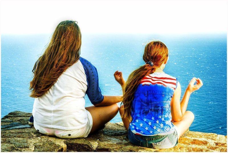 Dos chicas meditando en una pésima postura para meditar