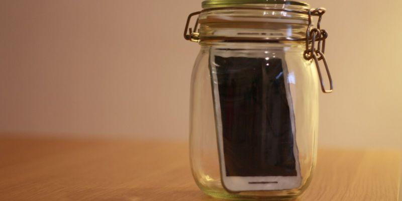 Fotografía de teléfono móvil metido en un bote de vidrio