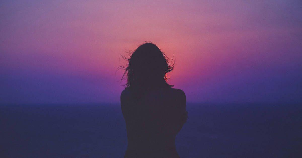 Fotografía de una mujer de espaldas observando el atardecer