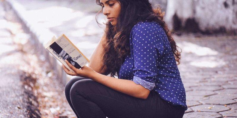 Mujer leyendo un libro sentada en la calle. Prasanna Kumar (Unsplash)