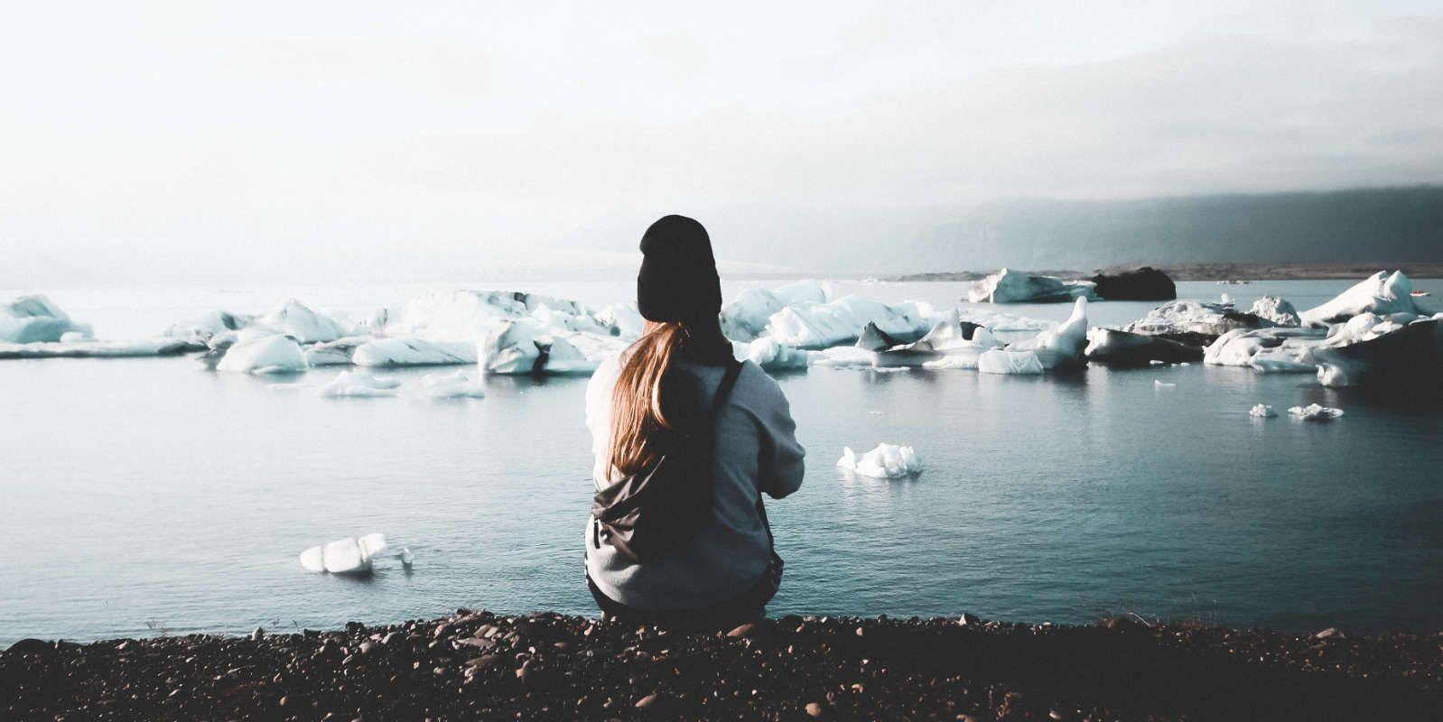 Chica sentada de espaldas mirando el mar con bloques de hielo