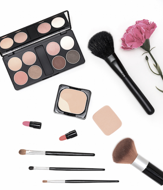 Makeup cosmetics palette and brushes on pink background