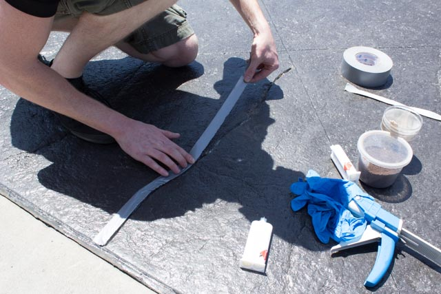 Masking off a crack to be repaired with MatchCrete Clear from Roadware.