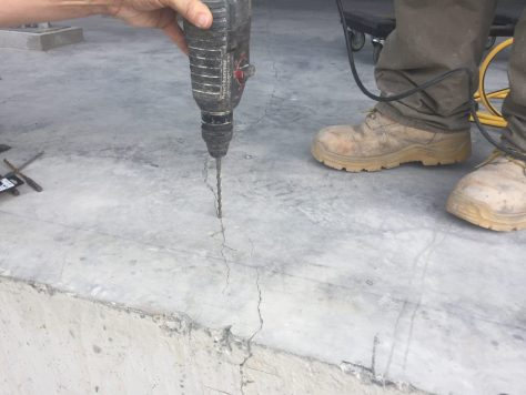 Drilling a pilot hole into a crack to prepare for injection with Roadware 10 Minute Concrete Mender.