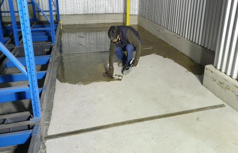 Craftsman trowel down a thin sealer coat of Roadware Freezer Floor Coating on to a prepared concrete floor at below freezing temperatures.