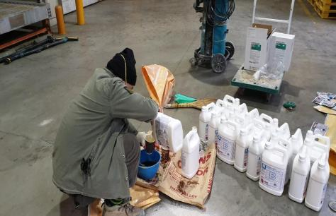 A craftsman mixes Roadware Freezer Floor Coating in a pail.