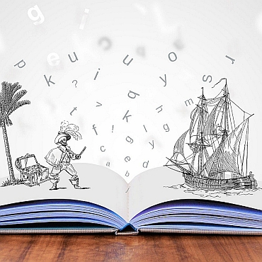 Open book on wood table with drawings of pirate and ship and letters rising out of it.