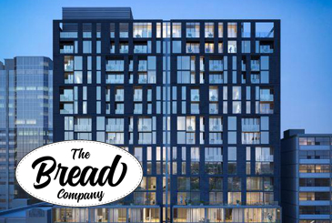 Exterior rendering of The Bread Company Condos with logo overlay.