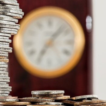A stack of coins with a blurry clock in the background.