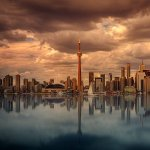 Toronto's skyline at waterfront with dark clouds above.