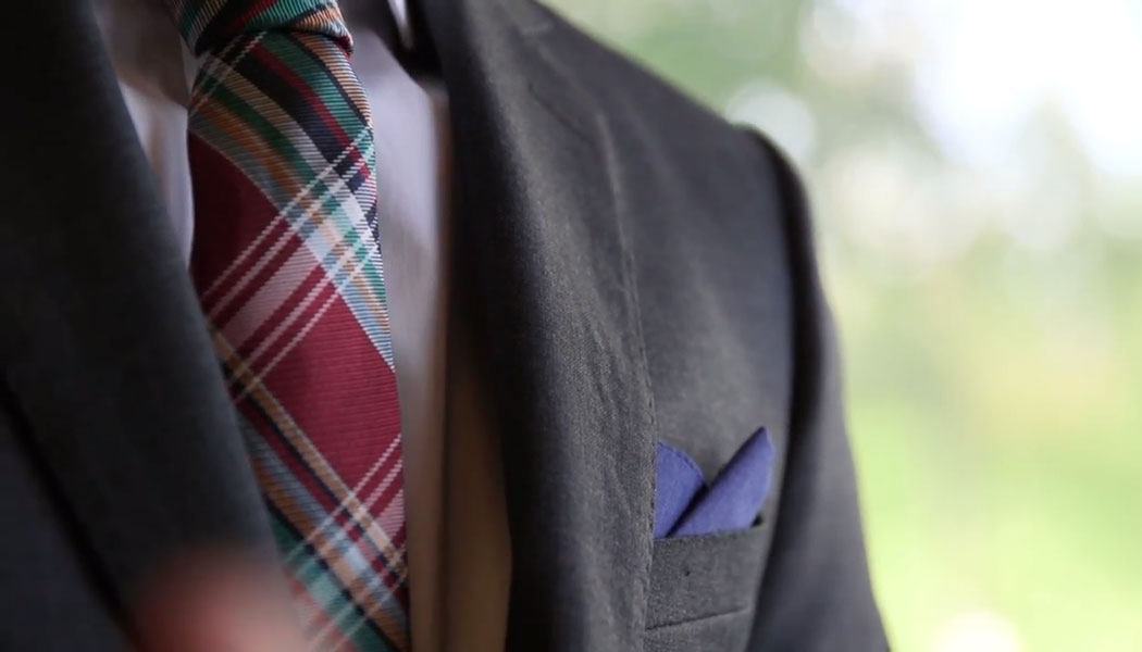 Shoulder of a well dressed man in a black suit with a plaid tie and navy blue pocket square.