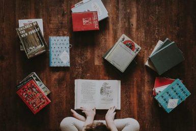 Child sitting on the floor reading books.