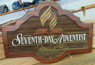 Cedar sign refinishing and restoration of the Vernon BC Seventh Day Adentist Church by Condor Signs Vernon BC