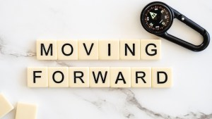 scrabble tiles spelling out the words moving forward with a compass on a clip in the corner of the image