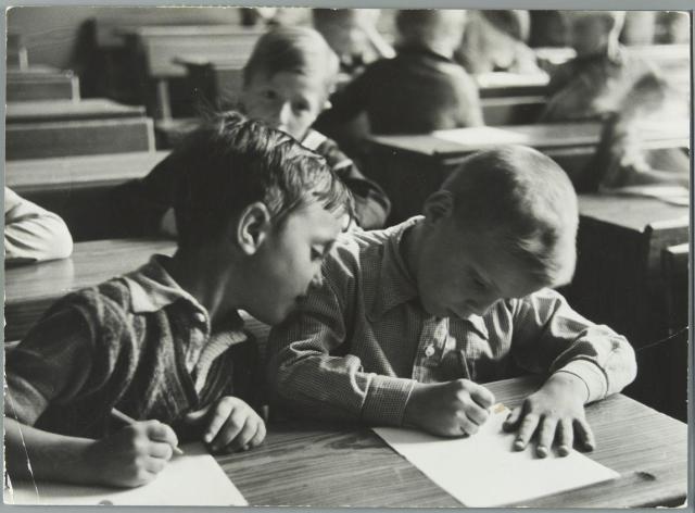 Kinderen met pen en papier in de schoolbank in de klas. [1937]. Plaats onbekend.