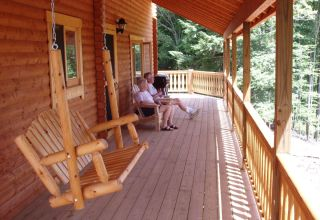 log cabin covered porch with swing