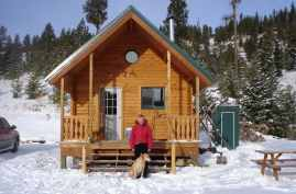 Outdoorsman log cabin in snow with pet