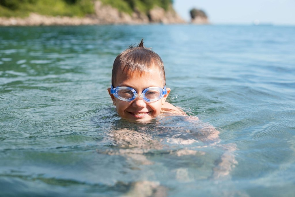 Boy with goggles treading water