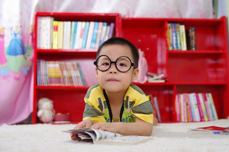 Child in large round glasses