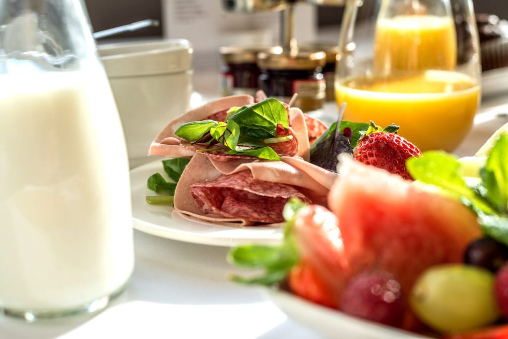 Close up of breakfast meats, fruit and salads on table with milk, orange juice and jam. Breakfast at Edgbaston Park Hotel.