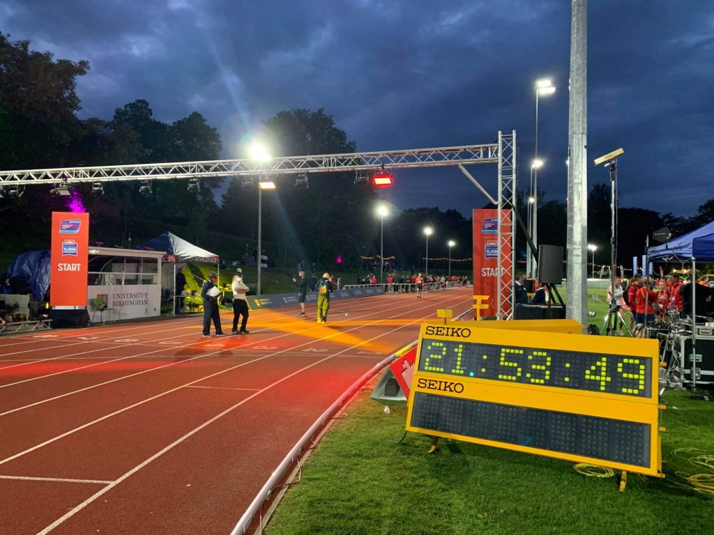 Athletics clock on track with officials and security in the background.