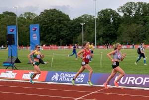 Student-athletes mid-run on the University of Birmingham's athletics track.