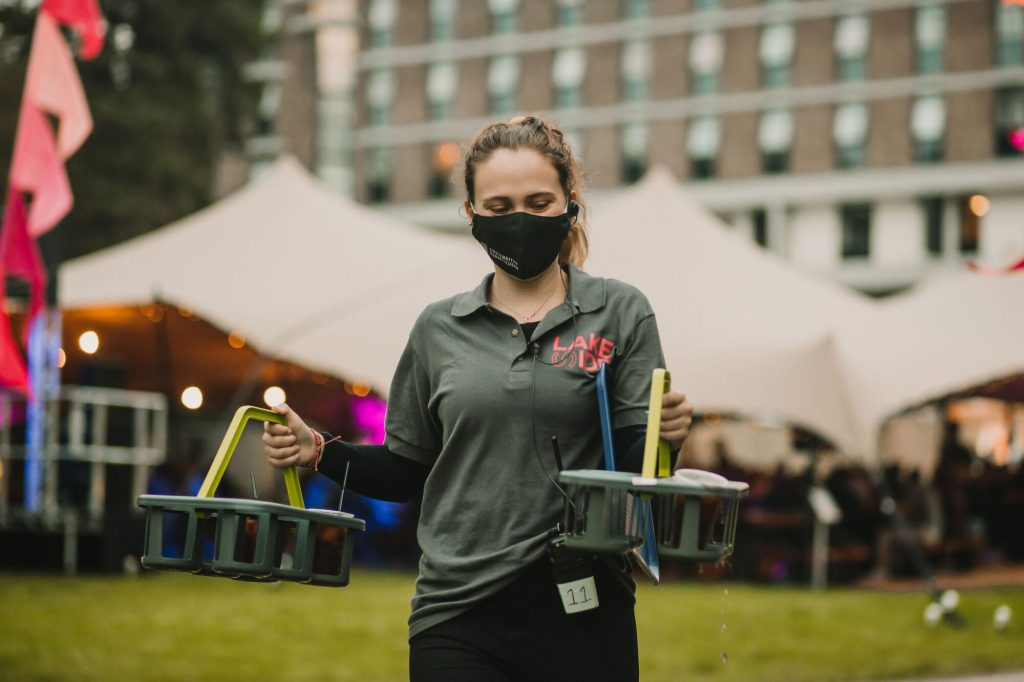 Woman wearing University of Birmingham face mask whilst carrying drinks at outdoor event.