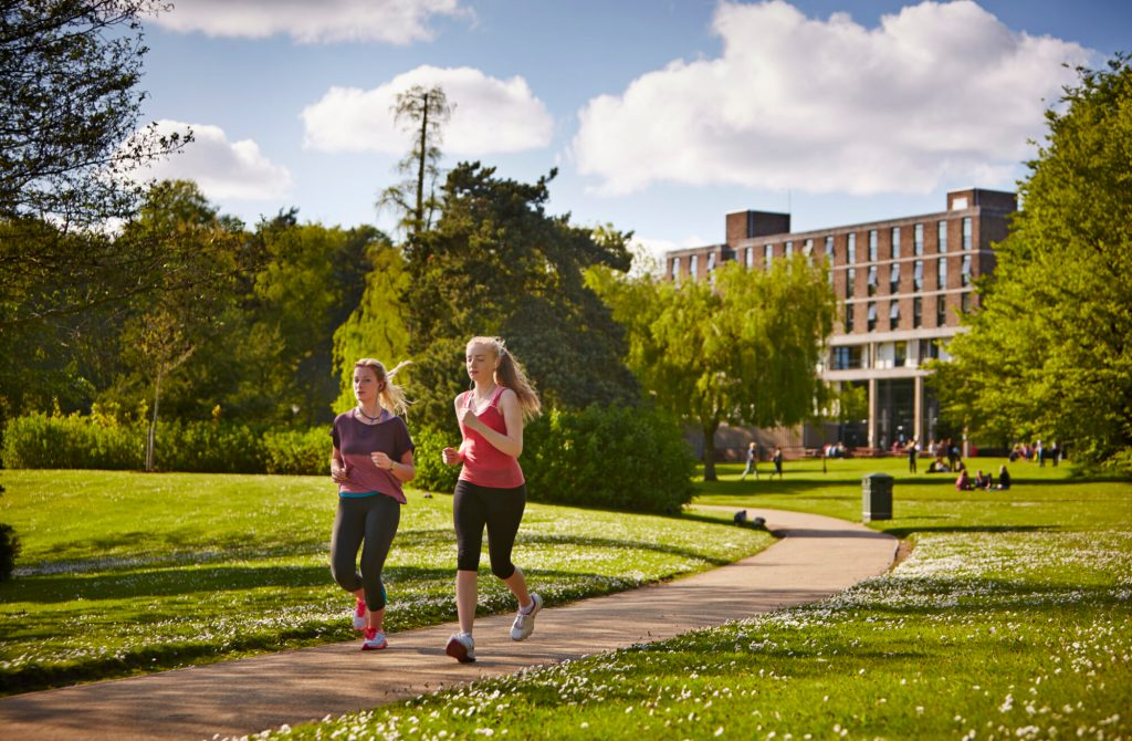 Two women running in the Vale's parkland,