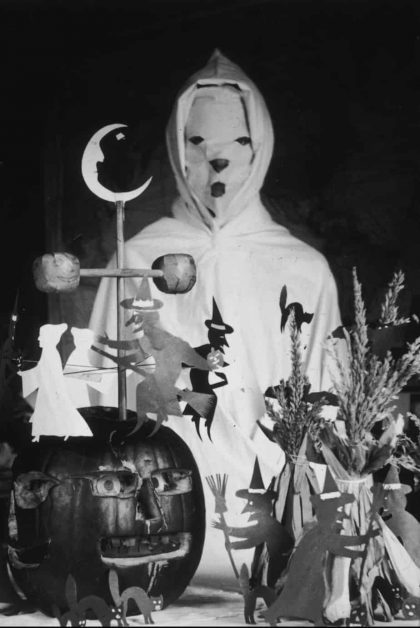 vintage halloween scene with man in white mask and robe and jackolanterns