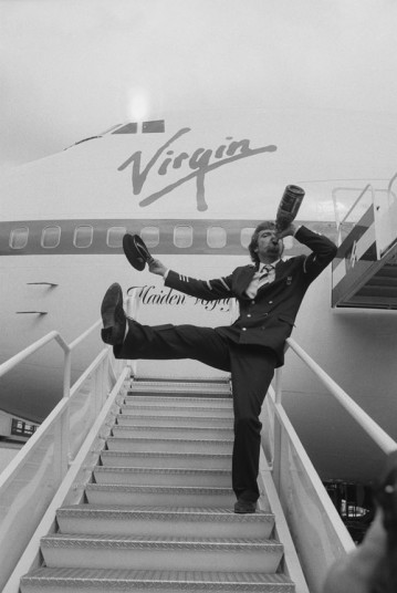 Branson celebrates on the steps of 'Maiden Voyager', with a bottle of champagne after the successful first flight.