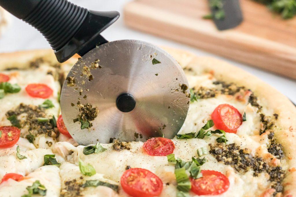 cutting chicken pesto pizza