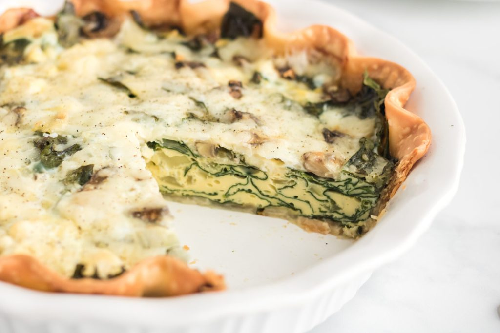 Quiche Florentine with slice taken out in white dish