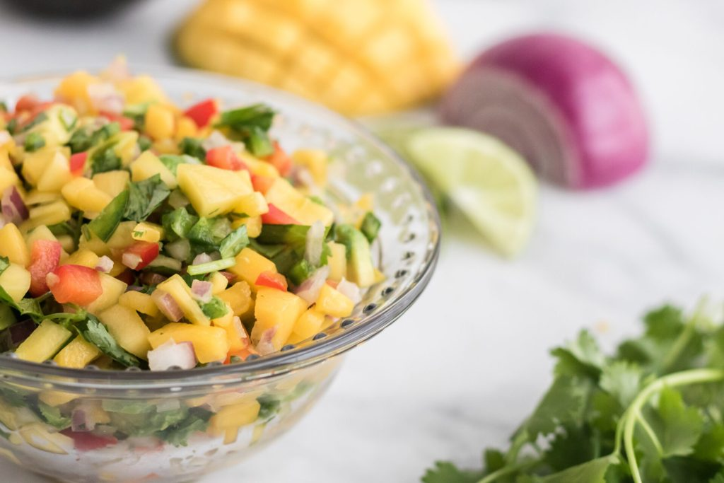 fresh mango salsa in bowl with onion, lime, mango, and cilantro in background