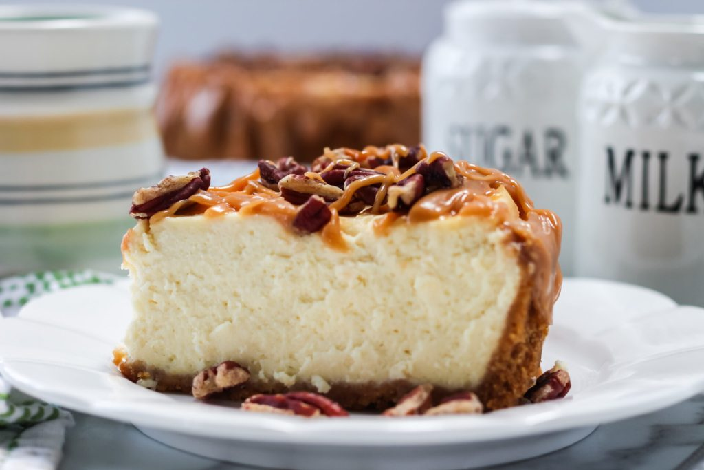 a slice of Salted caramel pecan cheesecake on a white plate.