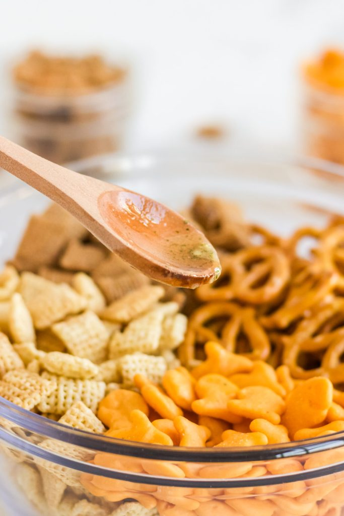 wooden spoon with sauce pouring on top of air fryer snack mix