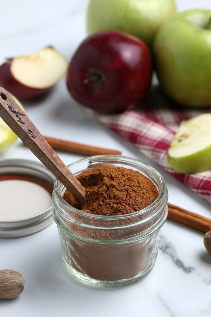 Vertical shot of apple pie spice mix with wooden spoon