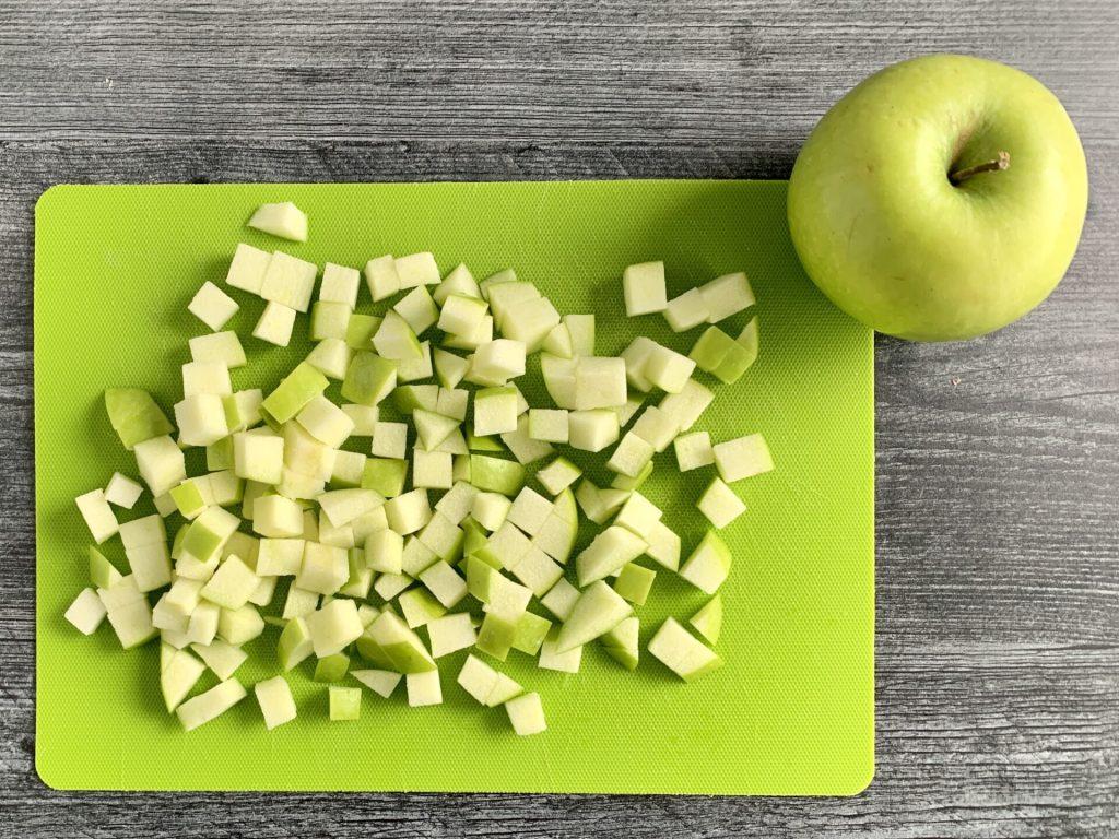 apples cut on a green cutting board