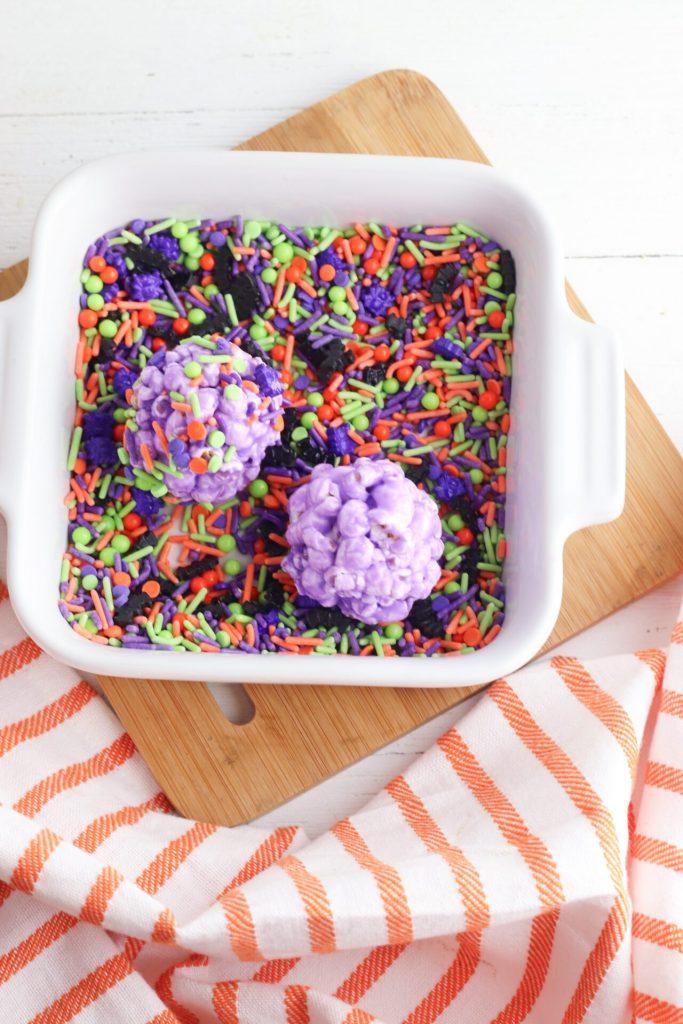 rolling DIY popcorn balls in sprinkles