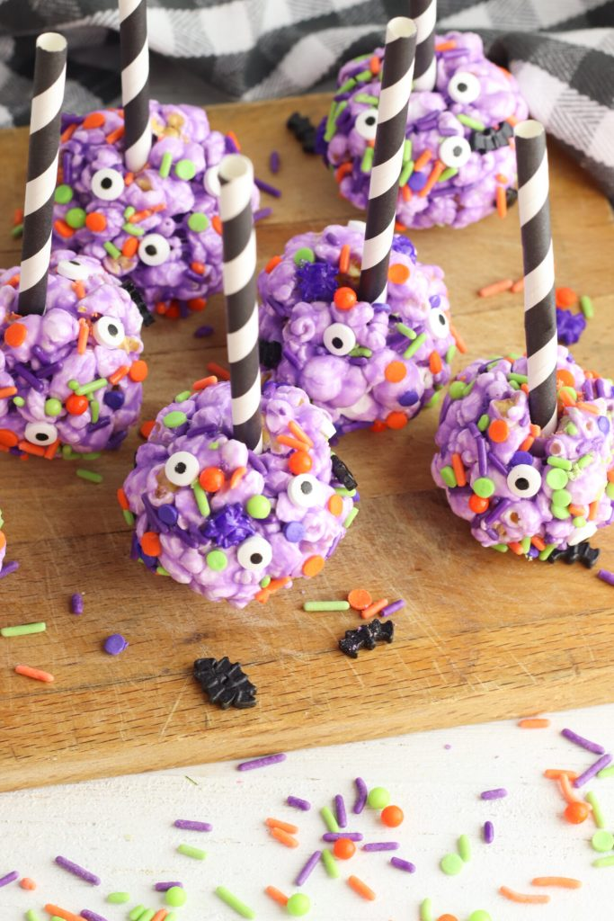 halloween pop corn balls with paper straws in them