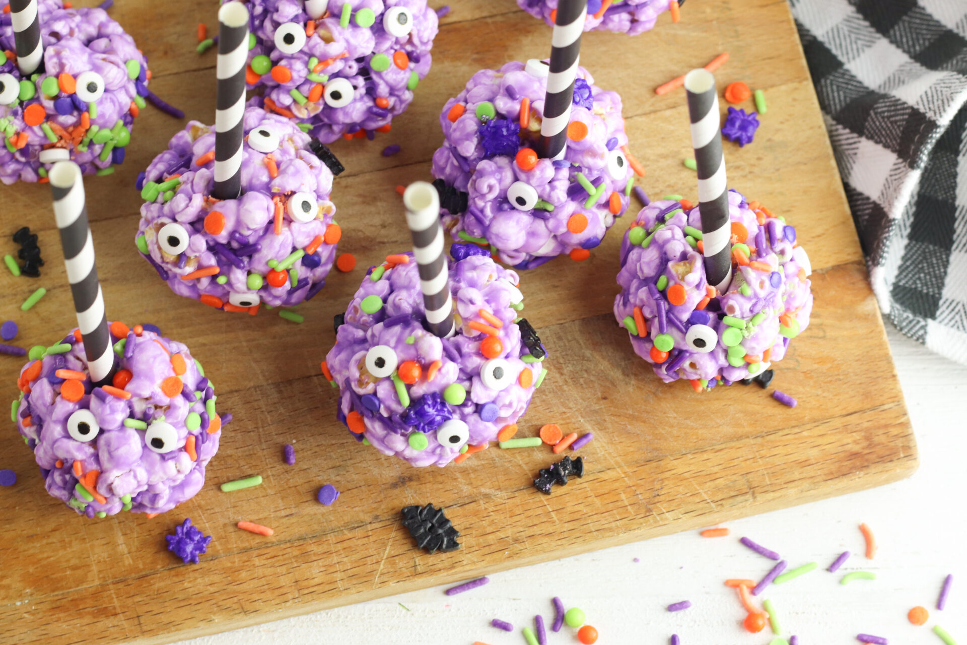 halloween popcorn balls on a wooden cutting board with black check linen