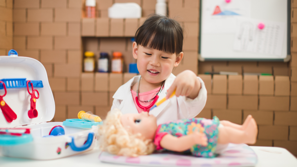 girl teaching her doll how to get toddler to take medicine